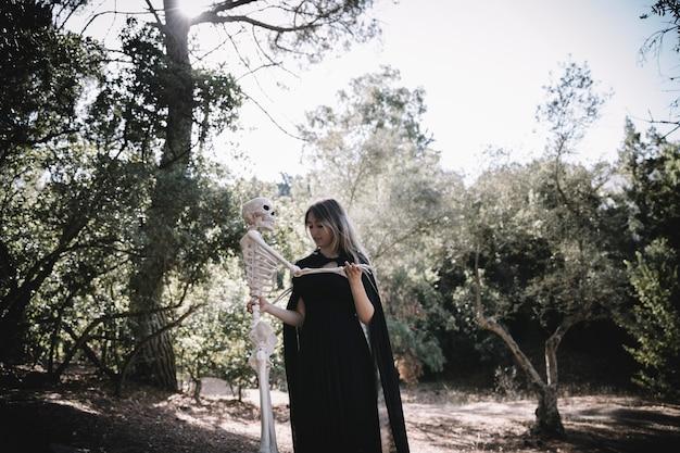 Femme En Costume De Sorcière Tenant Un Squelette Photo gratuit