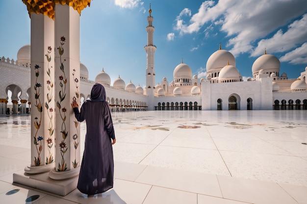 Femme en costume traditionnel à l'intérieur de la mosquée sheikh zayed. abu dhabi, emirats arabes unis. Photo Premium
