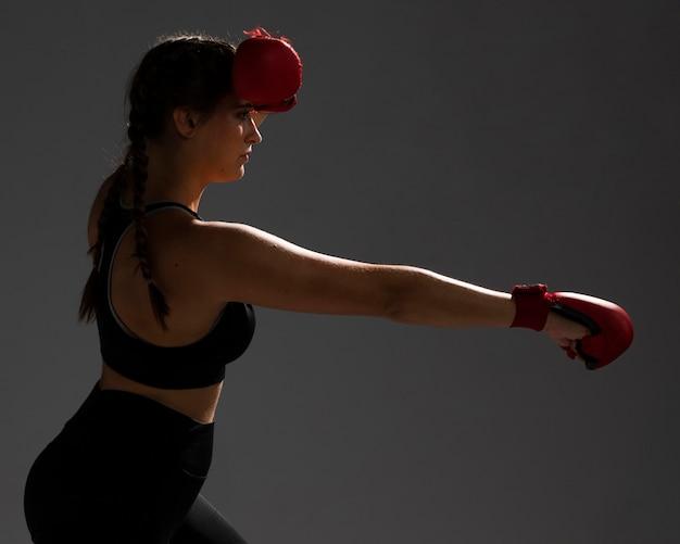 Femme de côté poinçonnant avec des gants Photo gratuit