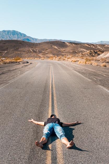 Une Femme Couchée Pieds Nus Sur Une Route Déserte Dans La Vallée De La Mort Photo Premium
