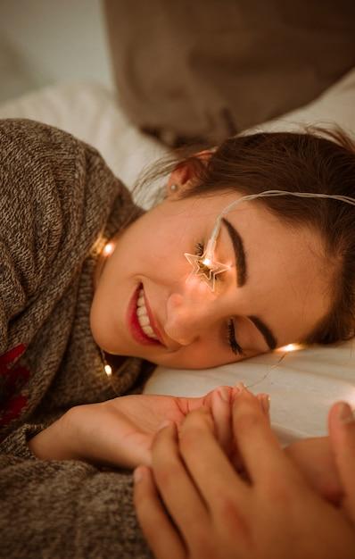 Femme, coucher lit, à, guirlande Photo gratuit
