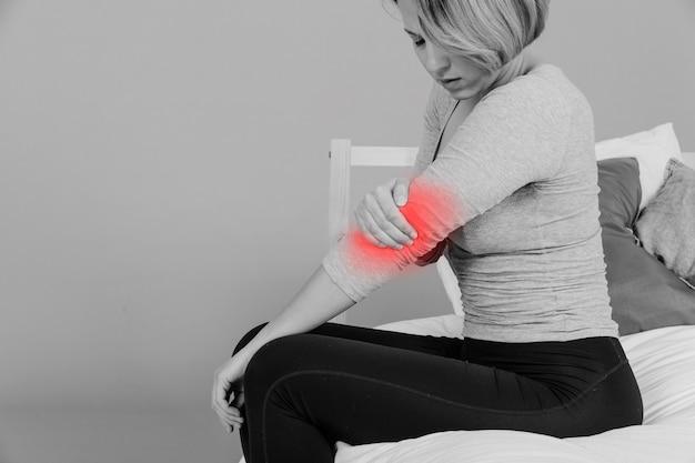Femme avec coude douloureux Photo gratuit