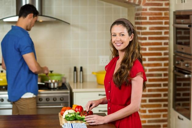 Femme, couper, legumes, et, cuisine, sur, cuisinière, dans, cuisine, à la maison Photo Premium