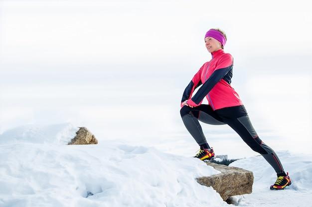 Femme coureur qui s'étend jambes avant de courir Photo Premium