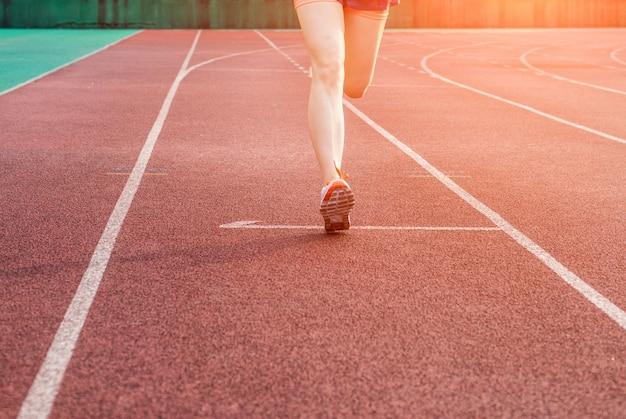 Femme Courir Sur Une Piste Sportive Photo gratuit