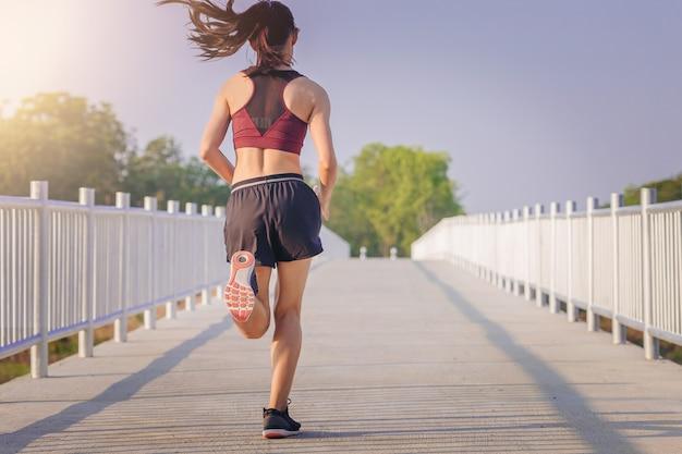 Femme, courir, sprinter, sur, route fit coureur de fitness féminin pendant l'entraînement en plein air Photo Premium