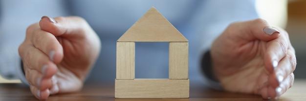 Femme Couvrant La Maison En Bois Avec Sa Main Gros Plan. Concept D'assurance Immobilière Photo Premium