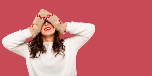 Femme couvrant ses yeux avec des gants moelleux Photo gratuit