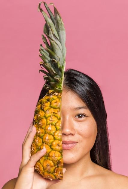 Femme Couvrant Son Visage à L'ananas Et Regardant La Caméra Photo gratuit