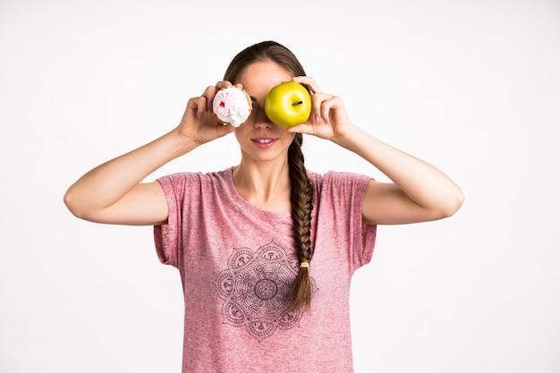 Femme couvrant son visage avec cupcake et pomme Photo gratuit