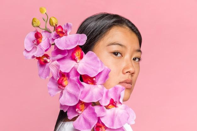 Femme couvrant son visage d'orchidée et regardant la caméra Photo gratuit