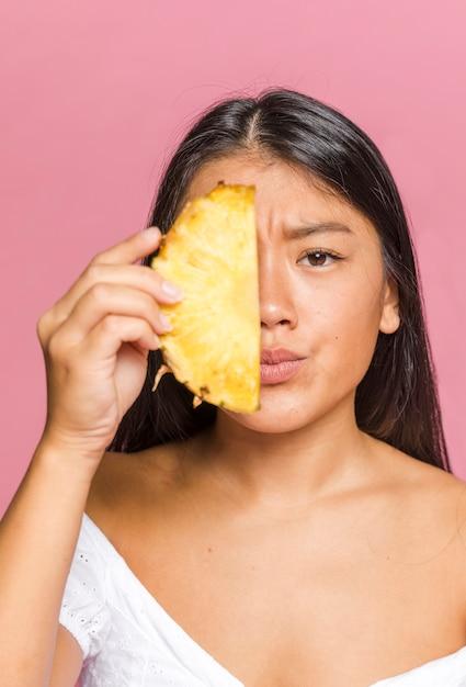 Femme Couvrant Son Visage Avec Des Tranches D'ananas Photo gratuit
