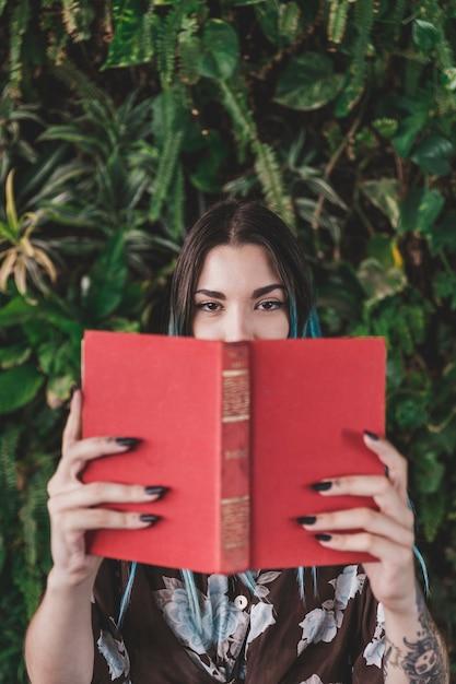 Femme, couvrir, bouche, livre, debout, croissant, plante Photo gratuit