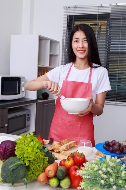 Femme, cuisine, fouetter, oeufs, bol, cuisine, salle Photo Premium