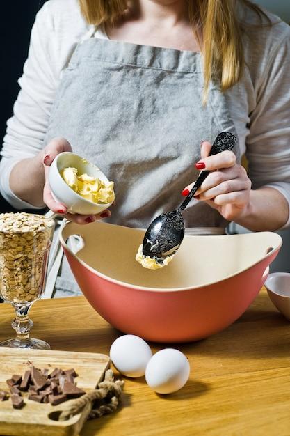 Femme cuisinier prépare des biscuits à l'avoine, met le beurre dans un bol. ingrédients flocons d'avoine, beurre, sucre, œufs, chocolat. Photo Premium
