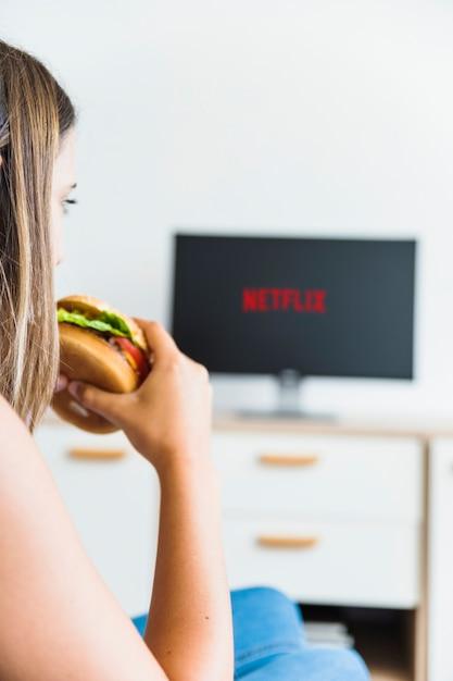 Femme de culture manger hamburger et regarder la série Photo gratuit