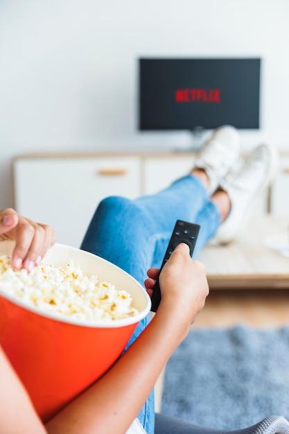 Femme de culture avec pop-corn regarder la série dans le salon Photo gratuit
