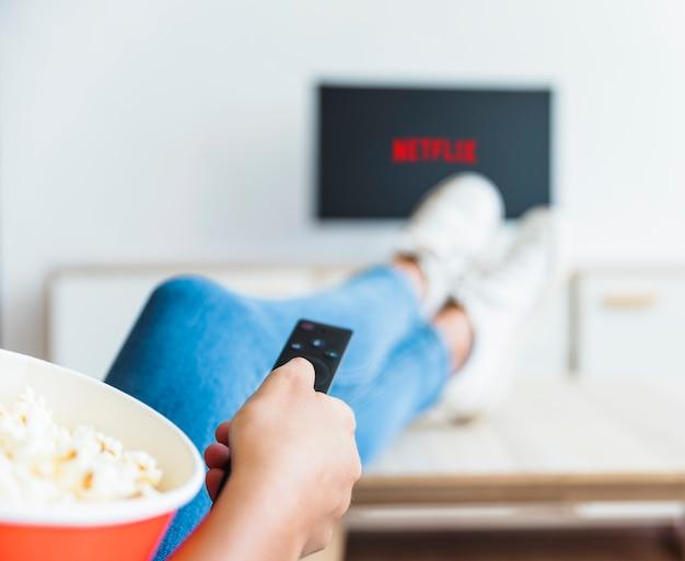 Femme de culture avec pop-corn en utilisant la télécommande à la télé Photo gratuit