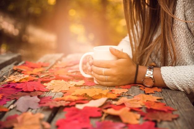 Femme de culture avec une tasse à table en automne parc Photo gratuit
