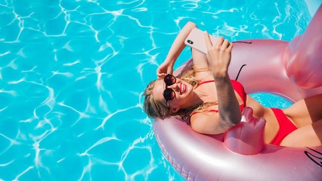 Femme dans l'anneau de nage flamingo avec espace copie Photo gratuit