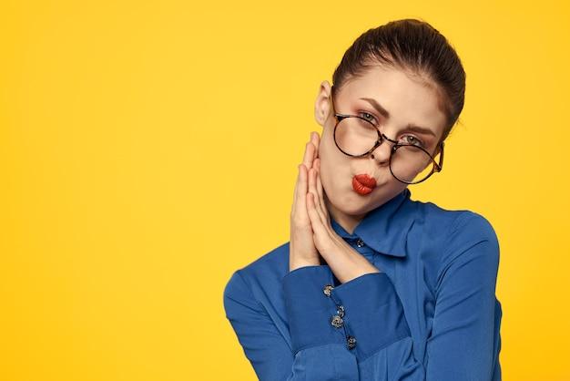 Une Femme Dans Une Chemise Bleue Et Des Lunettes Avec Un Maquillage Lumineux Sur Son Visage Fait Des Gestes Avec Ses Mains Sur Un Espace Jaune Copy Space. Photo Premium