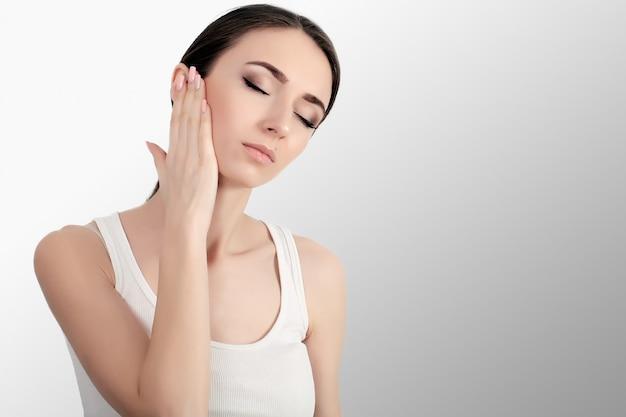 Femme dans la douleur. gros plan de belle jeune femme se sentir mal aux dents douloureuse, toucher le visage avec la main. fille stressée triste se sentant forte dents, mâchoire ou douleur au cou. santé et soins dentaires. Photo Premium