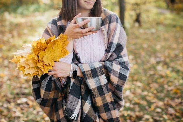 Femme Dans La Forêt D'automne, Boire Du Thé Avec Des Feuilles Dans Ses Mains Sun Photo Premium