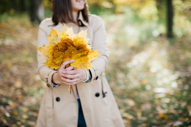 Femme Dans La Forêt D'automne Avec Des Feuilles Dans Ses Mains La Femme Est Heureuse Photo Premium