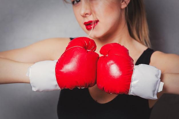 Femme dans des gants de boxe sur fond gris Photo Premium