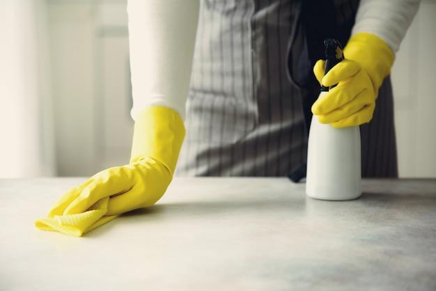 Femme dans des gants de protection en caoutchouc jaune, essuyant la poussière et sale. Photo Premium