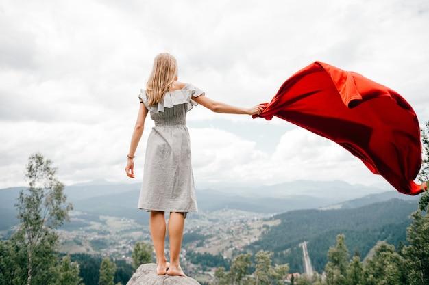 Femme Dans Les Montagnes Sauvages Donne Un Signal De Détresse Sos En Utilisant Une Couverture Rouge. Concept De Situation D'urgence Lors D'une Randonnée En Montagne. Femme Aux Pieds Nus Se Tient à La Pierre, Agitant Une Couverture Rouge Et Attendant De L'aide Photo Premium