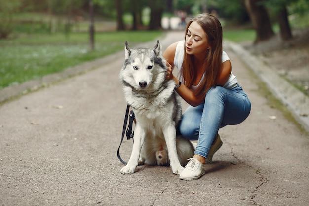 Femme dans un parc de printemps jouant avec un chien mignon Photo gratuit