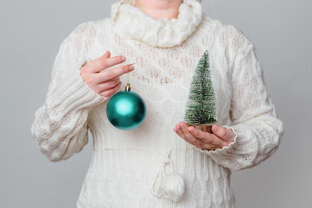Femme Dans Un Pull Blanc Tenant Une Boule De Noël Turquoise Et Pin Miniature Photo gratuit