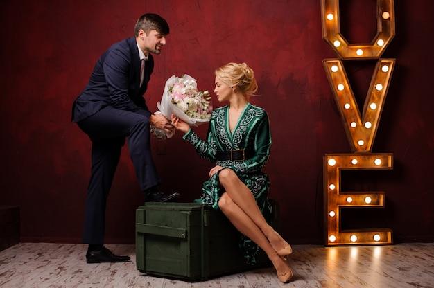 Femme Dans La Robe Verte Assise Sur La Boîte Obtient Un Bouquet Son Homme Photo Premium