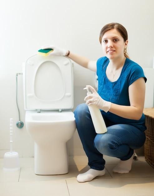 Femme dans la salle de bain avec une éponge et un nettoyant Photo gratuit