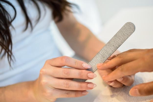 Femme dans un salon de manucure recevant une manucure avec une lime à ongles Photo gratuit