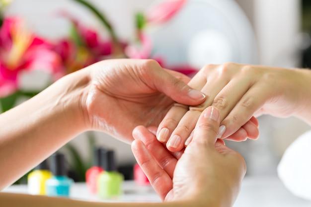 Femme dans un salon de manucure recevant un massage des mains Photo Premium