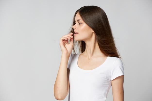 Femme Dans Un T-shirt Blanc, Il Regarde Sur Le Côté Les Cheveux Longs Main Près Du Visage Photo Premium