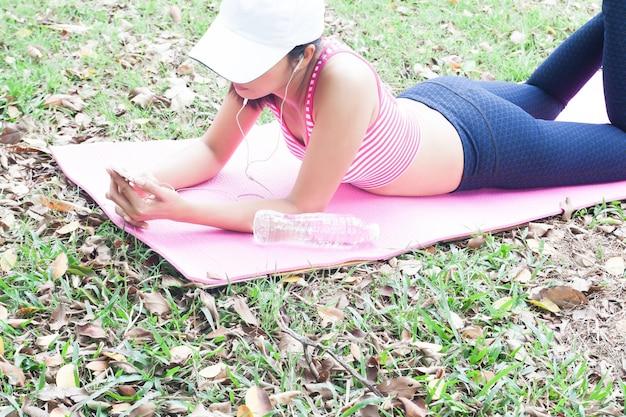 Femme Dans Des Vêtements De Yoga à L'aide De Smartphone, Se Détendre Dans Le Parc, Mode De Vie Sain Photo Premium