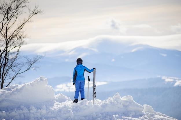 Femme debout au sommet de la montagne et profitant de la vue sur les belles montagnes en hiver Photo Premium