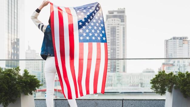 Femme, debout, balcon, grand, drapeau américain Photo gratuit