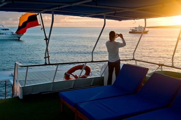 Femme, debout, sur, a, bateau, et, photographier, punta suarez, île espanola, îles galapagos, équateur Photo Premium