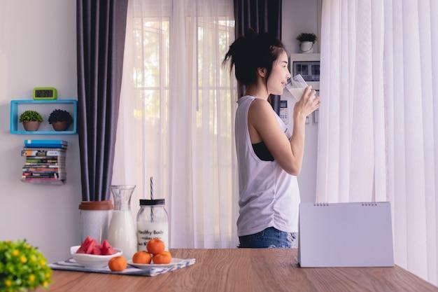 Femme debout, buvant du lait dans le salon à la maison, style de vie de jeune femme asiatique. Photo Premium