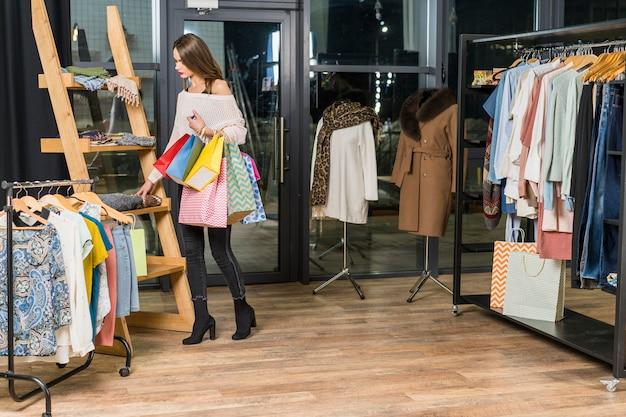 Femme debout dans un magasin de vêtements, tenant des sacs en papier dans la main Photo gratuit