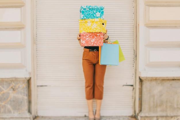Femme debout derrière des boîtes avec des achats Photo gratuit