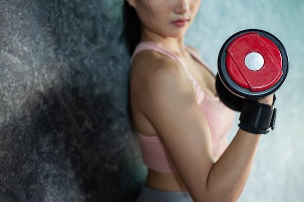 Femme debout exerçant avec un haltère rouge dans la salle de gym. Photo gratuit