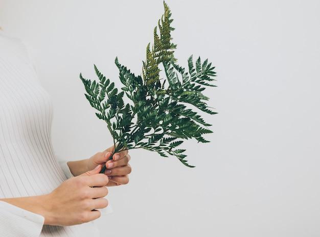 Femme debout avec des feuilles de fougère Photo gratuit