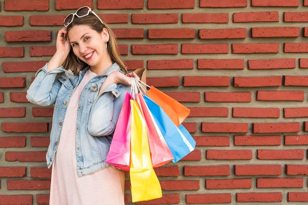 Femme, debout, à, lumineux, sacs shopping, derrière, à, mur brique Photo gratuit