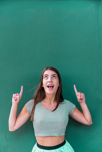 Femme debout et pointant vers le haut sur un espace vide au-dessus de la tête Photo gratuit