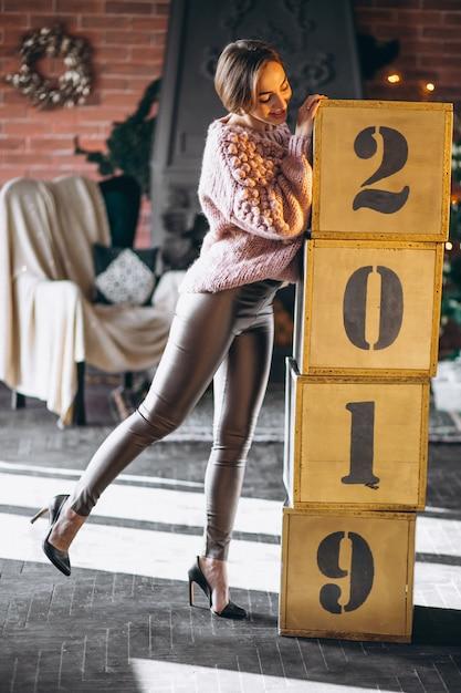 Femme debout près des boîtes 2019 à noël Photo gratuit